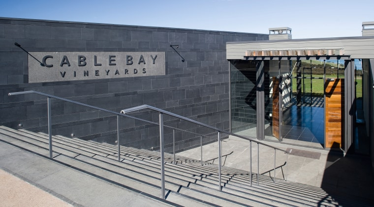 The entrance brings patrons downstairs into a foyer architecture, building, structure, gray