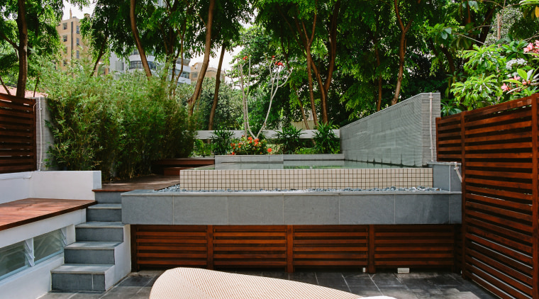 A view of this outdoor entertainment area featuring backyard, courtyard, estate, furniture, house, landscaping, outdoor furniture, outdoor structure, patio, plant, property, real estate, table, walkway, wall, yard