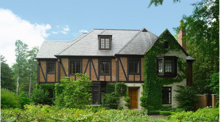 An exterior view of this traditional tudor style cottage, estate, facade, farmhouse, home, house, property, real estate, residential area, roof, siding, tree, green, teal