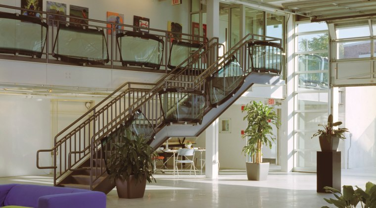 A large roller door on the south facade handrail, interior design, lobby, stairs, structure, gray, brown