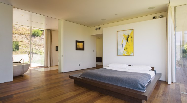 A view of this master bedroom featuring brazilian architecture, bed, bed frame, bedroom, ceiling, estate, floor, flooring, hardwood, house, interior design, laminate flooring, property, real estate, room, wood, wood flooring, gray, brown