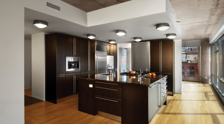 A view of an apartment complex developed by cabinetry, ceiling, countertop, floor, flooring, hardwood, interior design, kitchen, laminate flooring, wood flooring, gray