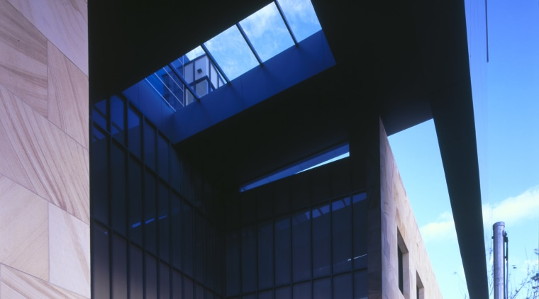 A deep overhead canopy covers the entrance to architecture, building, commercial building, corporate headquarters, daylighting, daytime, facade, glass, headquarters, house, mixed use, sky, structure, black, blue