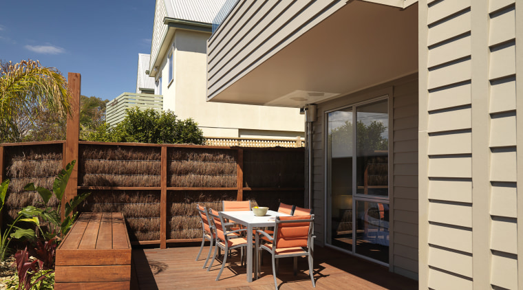 An exterior of this house featuring Merbau decking, deck, home, house, outdoor structure, real estate, residential area, siding, orange