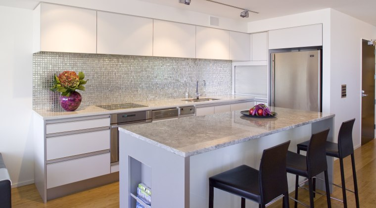View of kitchen featuring wall tiling, kitchen island, cabinetry, countertop, floor, flooring, interior design, kitchen, real estate, room, gray