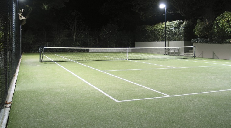 Image of a residential tennis court which was artificial turf, ball game, grass, net, plant, racquet sport, real tennis, sport venue, sports, structure, tennis, tennis court, green, black