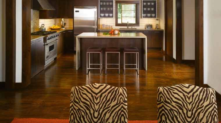 The color scheme of golds and browns gives floor, flooring, hardwood, interior design, kitchen, laminate flooring, living room, room, wood, wood flooring, brown