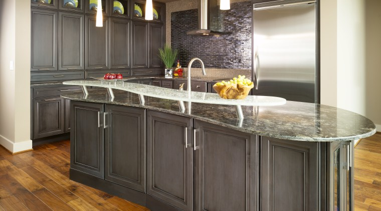 The placement of the island was confined by cabinetry, countertop, cuisine classique, floor, flooring, hardwood, interior design, kitchen, room, wood flooring