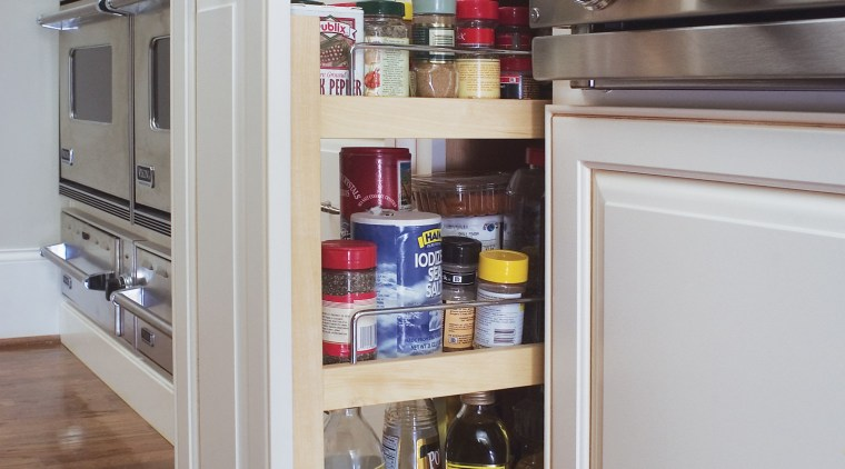 Soft white cabinets are paired with a cherry cabinetry, kitchen, refrigerator, shelf, shelving, gray