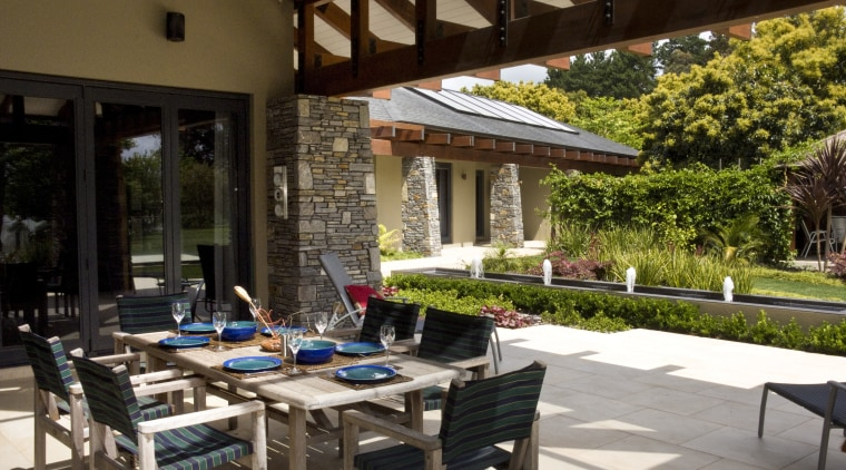 View of the patio area which features outdoor backyard, courtyard, outdoor structure, patio, table, brown, black