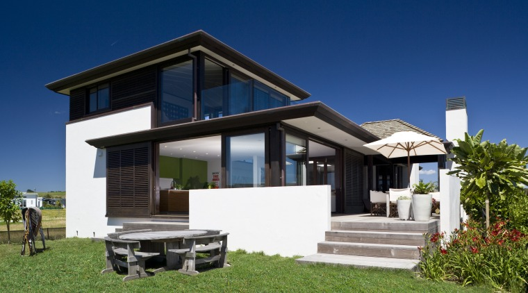 Exterior view of bach which features a shingle architecture, cottage, elevation, estate, facade, home, house, property, real estate, residential area, sky, villa, blue