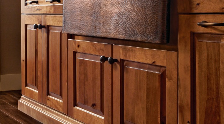 View of a kitchen which features wooden cabinetry cabinetry, chest of drawers, countertop, drawer, floor, flooring, furniture, hardwood, laminate flooring, sideboard, tile, wood, wood flooring, wood stain, brown