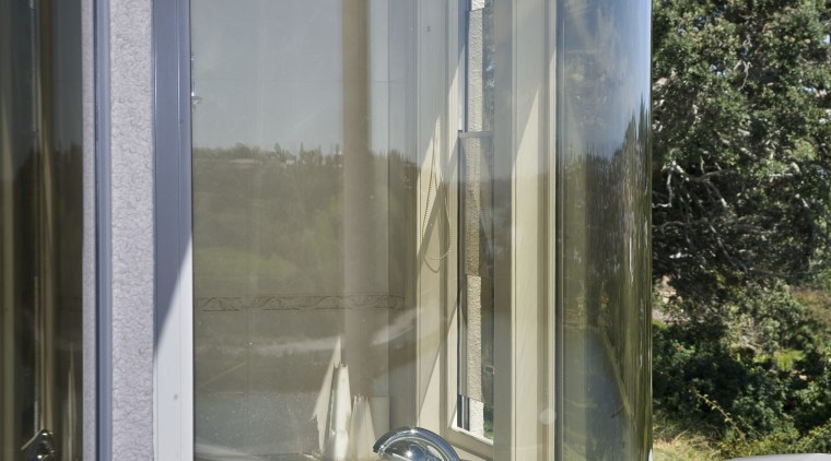 View of a curved bathroom window which was glass, window, gray