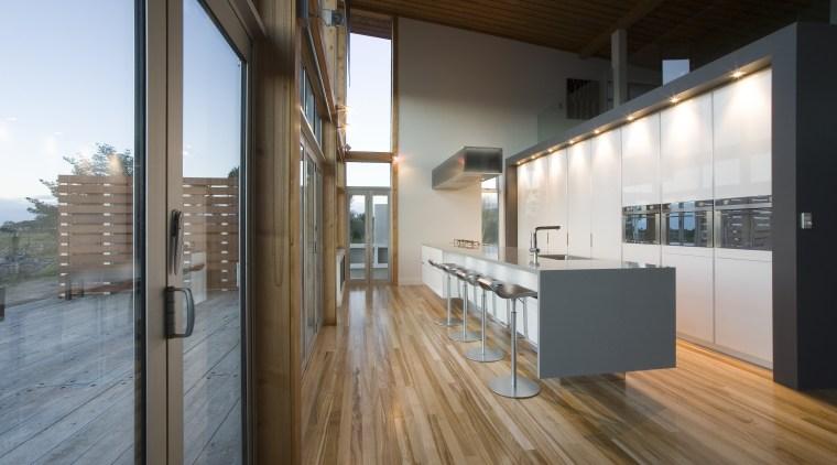View of a kitchen designed by NKBA designer apartment, architecture, daylighting, floor, flooring, hardwood, house, interior design, loft, real estate, wood, wood flooring, brown