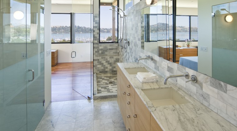 View of a bathroom which features a marble bathroom, countertop, floor, flooring, glass, interior design, real estate, room, tile, window, gray