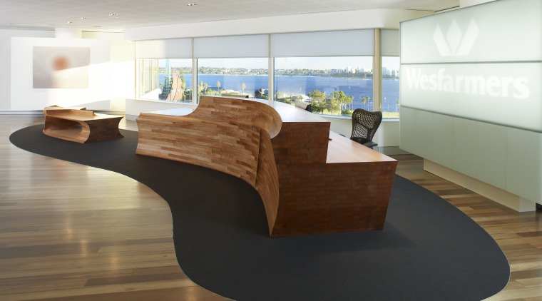 View of the reception area which features a desk, floor, flooring, furniture, hardwood, interior design, office, product design, table, wood, brown