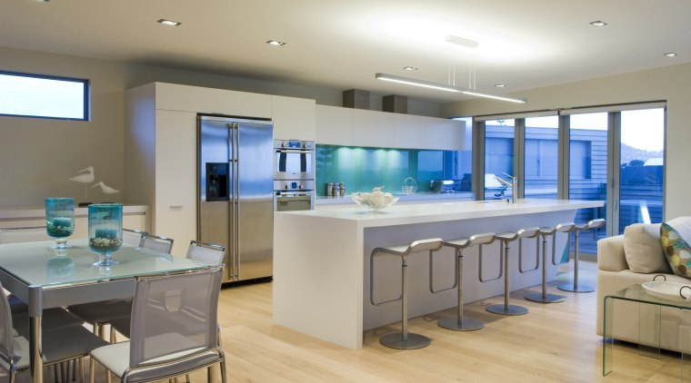This sleek kitchen in a beach house features countertop, interior design, kitchen, real estate, room, gray