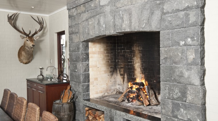 In the dining area of the home this fireplace, hearth, interior design, wood burning stove, gray