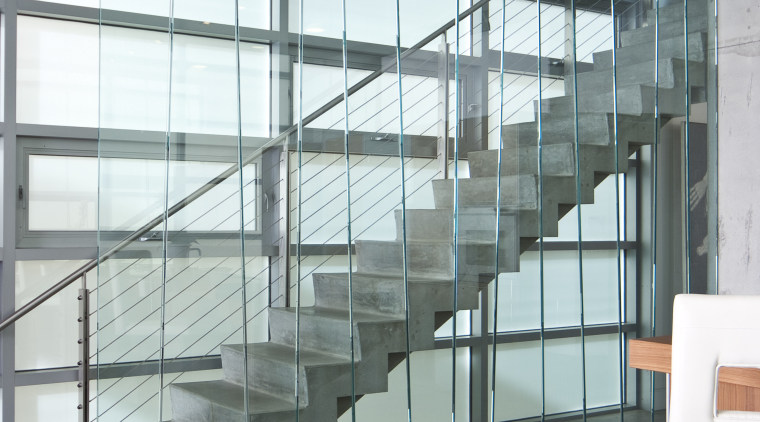 View of living space and staircase featuring vertical architecture, daylighting, glass, handrail, interior design, stairs, window, gray