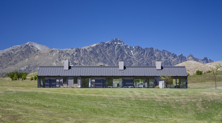 Exterior view of a country home which features alps, barn, cottage, elevation, estate, farm, farmhouse, field, grass, grassland, highland, home, house, hut, land lot, landscape, meadow, mount scenery, mountain, mountain range, mountainous landforms, national park, pasture, property, ranch, real estate, roof, rural area, sky, blue