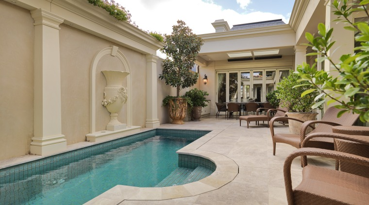 View of this pool and patio features outdoor apartment, estate, hacienda, home, house, leisure, property, real estate, resort, swimming pool, villa, gray, brown