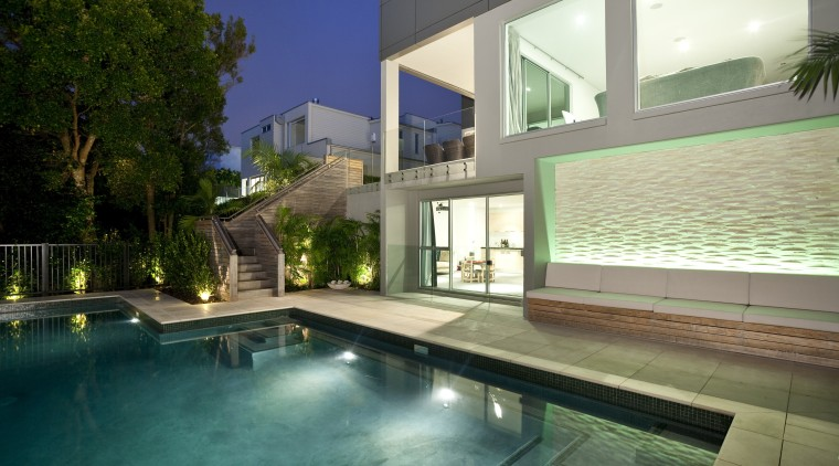 View of sleek poolscape with textured stone wall, apartment, architecture, condominium, estate, home, house, interior design, lighting, property, real estate, residential area, swimming pool, villa, window