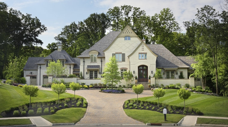 Exterior view of this large traditional home features cottage, estate, facade, farmhouse, grass, historic house, home, house, land lot, landscape, landscaping, lawn, manor house, mansion, neighbourhood, plantation, property, real estate, residential area, suburb, tree, walkway, yard, gray