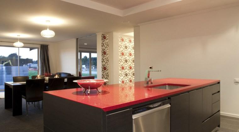 View of kitchen area which features kitchen island architecture, ceiling, countertop, daylighting, floor, flooring, interior design, kitchen, lighting, real estate, room, table, orange, black