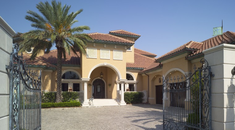 Exterior view of an Italian villa-styled waterfront home. arecales, building, estate, facade, hacienda, home, house, mansion, palm tree, property, real estate, residential area, villa, gray, teal