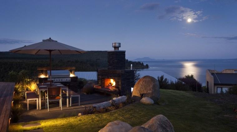 Evening view of the contemporary home cottage, dusk, estate, evening, home, horizon, lighting, property, real estate, resort, sea, sky, villa, blue, black