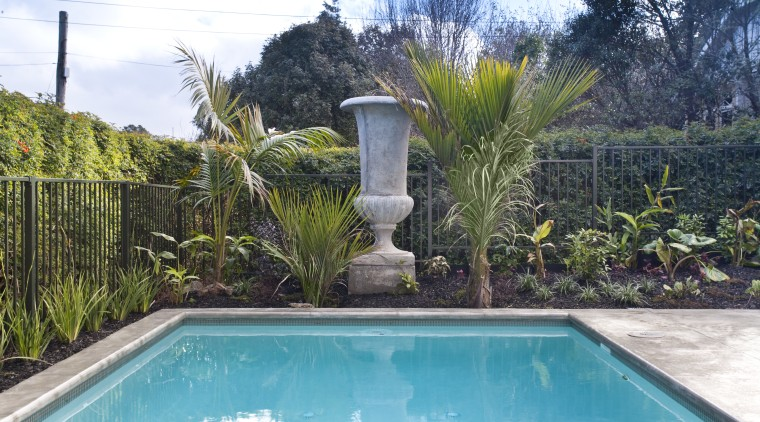 View of traditional outdoor pool area. Many plants arecales, backyard, estate, fence, garden, house, landscape, landscaping, outdoor structure, palm tree, plant, property, real estate, reflecting pool, swimming pool, tree, villa, water, yard