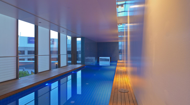 View of indoor cantilevered pool featuring wooden seating, apartment, architecture, blue, daylighting, house, interior design, light, lighting, real estate, reflection, blue