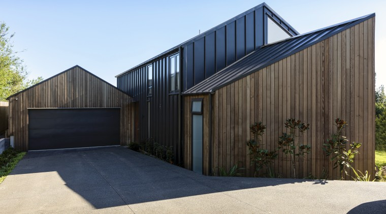 By strategic positioning of the core of the architecture, barn, building, door, facade, garage, home, house, land lot, property, real estate, residential area, roof, shed, siding, tree, black, teal