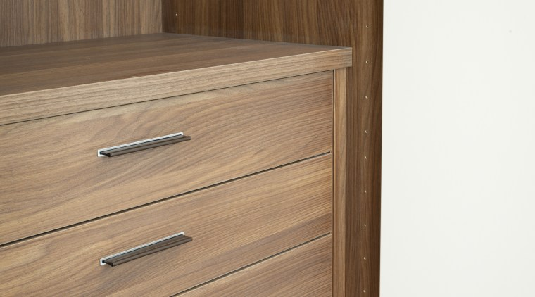 View of an apartment which features cabinetry by chest of drawers, door, drawer, furniture, hardwood, wood, wood stain, brown, white