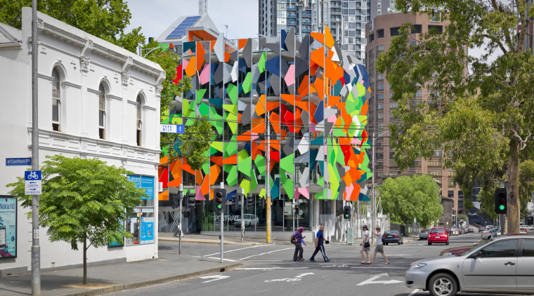View of Pixel Building, with colorful exterior flags, advertising, city, facade, mixed use, mural, neighbourhood, road, street, tree, urban area, wall, gray