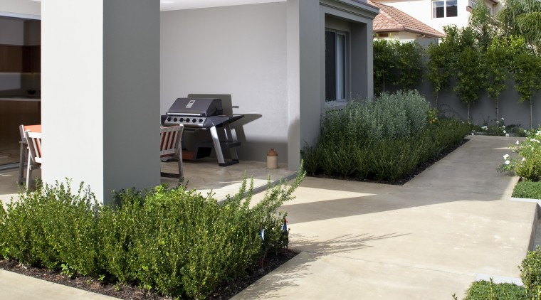 View of neutral-toned Peter Fell home backyard, building, courtyard, estate, facade, home, house, landscaping, property, real estate, residential area, siding, villa, window, yard, white