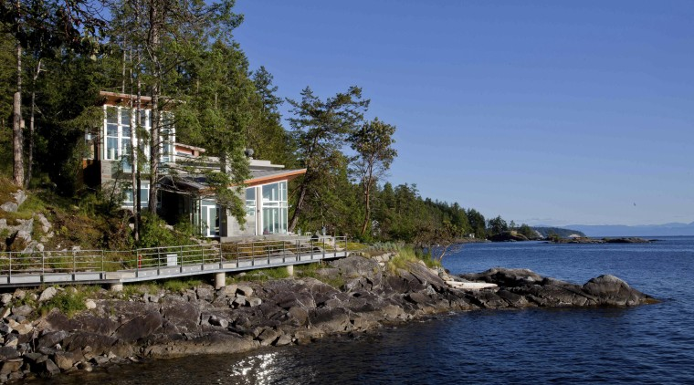 View of waterfront house. bay, coast, cottage, home, house, inlet, lake, real estate, sea, shore, sky, tree, water, blue