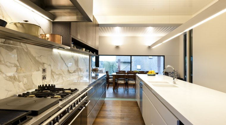 Stainless steel appliances. Minimalistic design. Indoor- outdoor flow. countertop, interior design, kitchen, white, orange