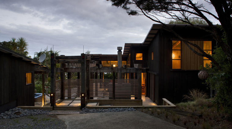 The timber for this house is treated with architecture, building, cottage, evening, facade, home, house, lighting, real estate, residential area, black, gray
