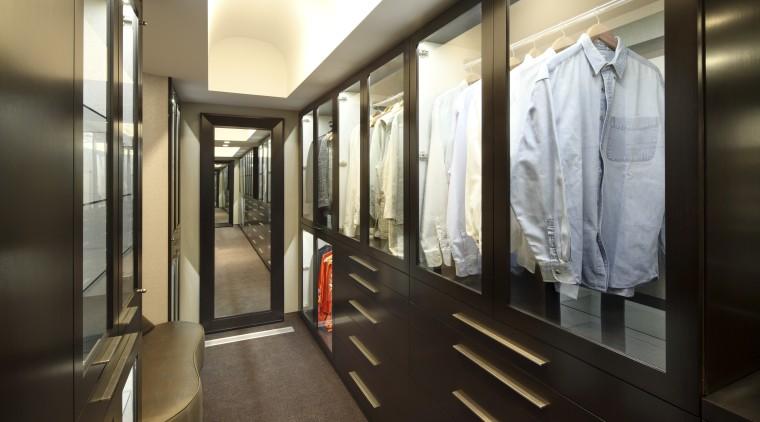 View of contempoary walk in wardrobe with dark boutique, furniture, interior design, lobby, black