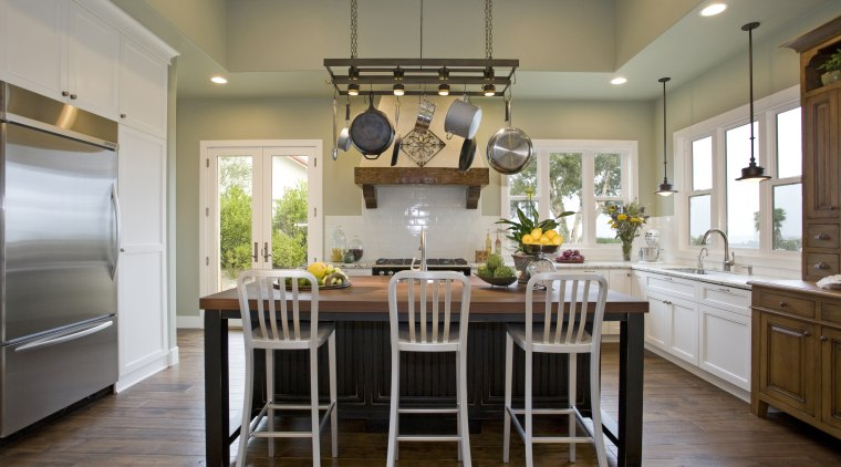View of kitchen with wooden flooring, hanging pots cabinetry, ceiling, countertop, cuisine classique, dining room, interior design, kitchen, room, table, gray, brown