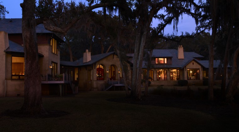 Exterior night shot of house with landscaping. cottage, darkness, estate, evening, home, house, landscape lighting, light, lighting, night, property, real estate, residential area, sky, town, tree, black