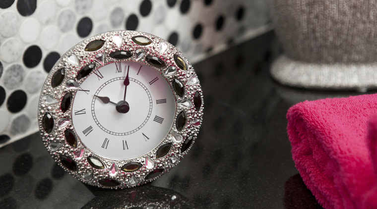 View of round clock with pink towel and bling bling, close up, jewellery, pink, watch, black, gray