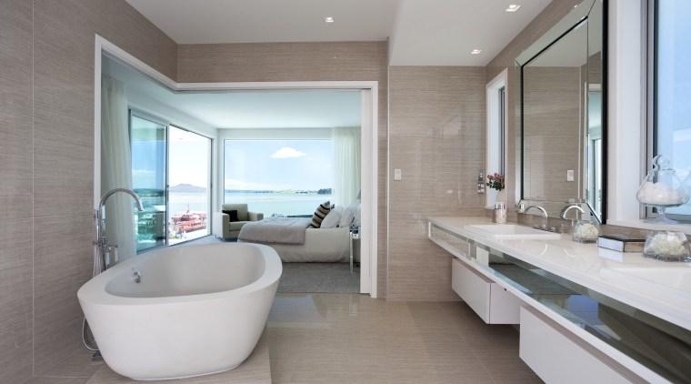 Beige bathroom with large white tub. - Beige architecture, bathroom, estate, floor, home, interior design, property, real estate, room, suite, window, gray