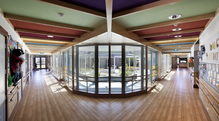 View of forked hallways with wooden flooring. ceiling, daylighting, floor, flooring, interior design, lobby, real estate, brown, gray