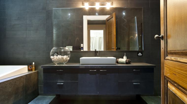 Bathroom with dark grey walls, dark vanity and bathroom, cabinetry, countertop, interior design, room, sink, black
