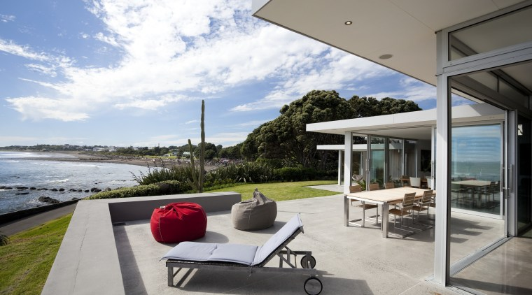 Outdoor view, patio overlooking beach, outdoor furniture, glass architecture, home, house, interior design, outdoor furniture, property, real estate, sunlounger, vacation, window, gray