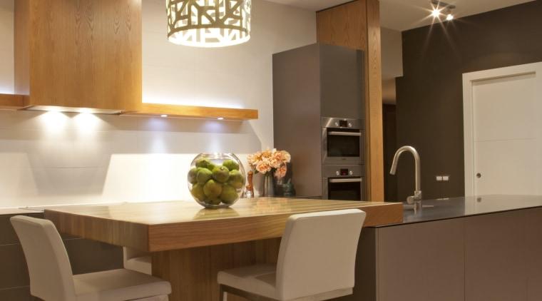 The David Trubridge lamp above this breakfast bar cabinetry, ceiling, countertop, cuisine classique, furniture, interior design, kitchen, light fixture, lighting, table, brown, orange