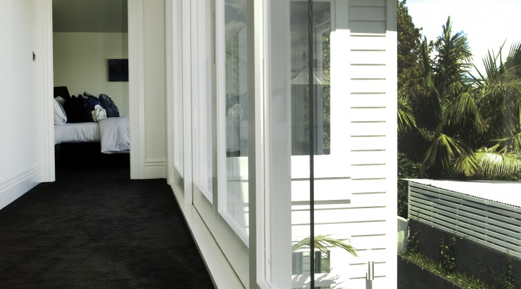 Hallway with black carpet and white walls. architecture, daylighting, estate, home, house, interior design, property, real estate, window, gray, black