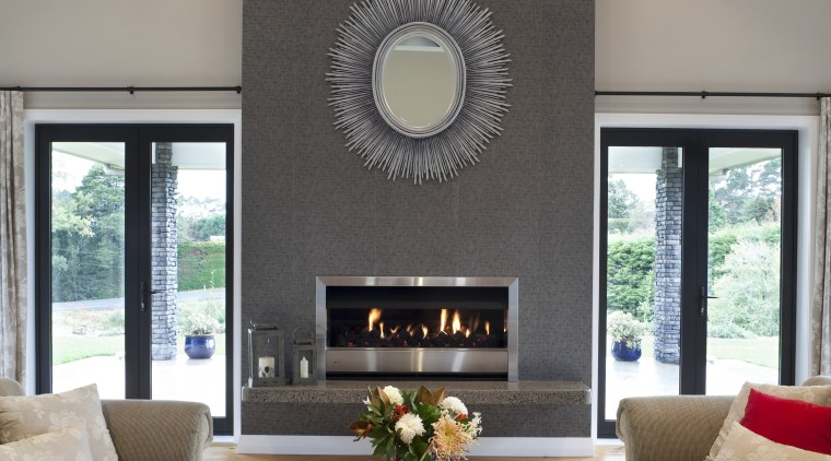lounge with fireplace and circular mirror, tw couches ceiling, hearth, home, house, interior design, living room, room, table, gray